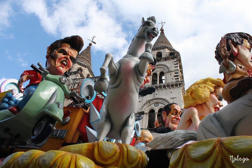 Un carro di personaggi famosi sotto il cielo azzurro di Acireale.